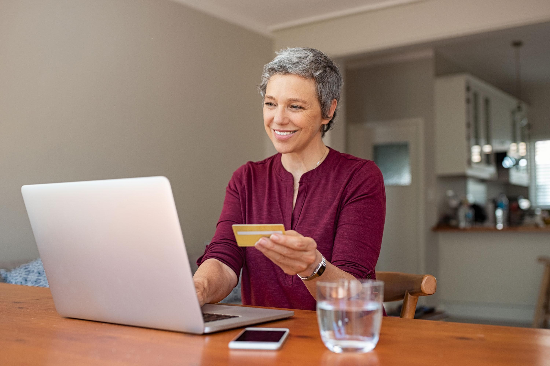 Photo of senior woman paying bills on laptop computer