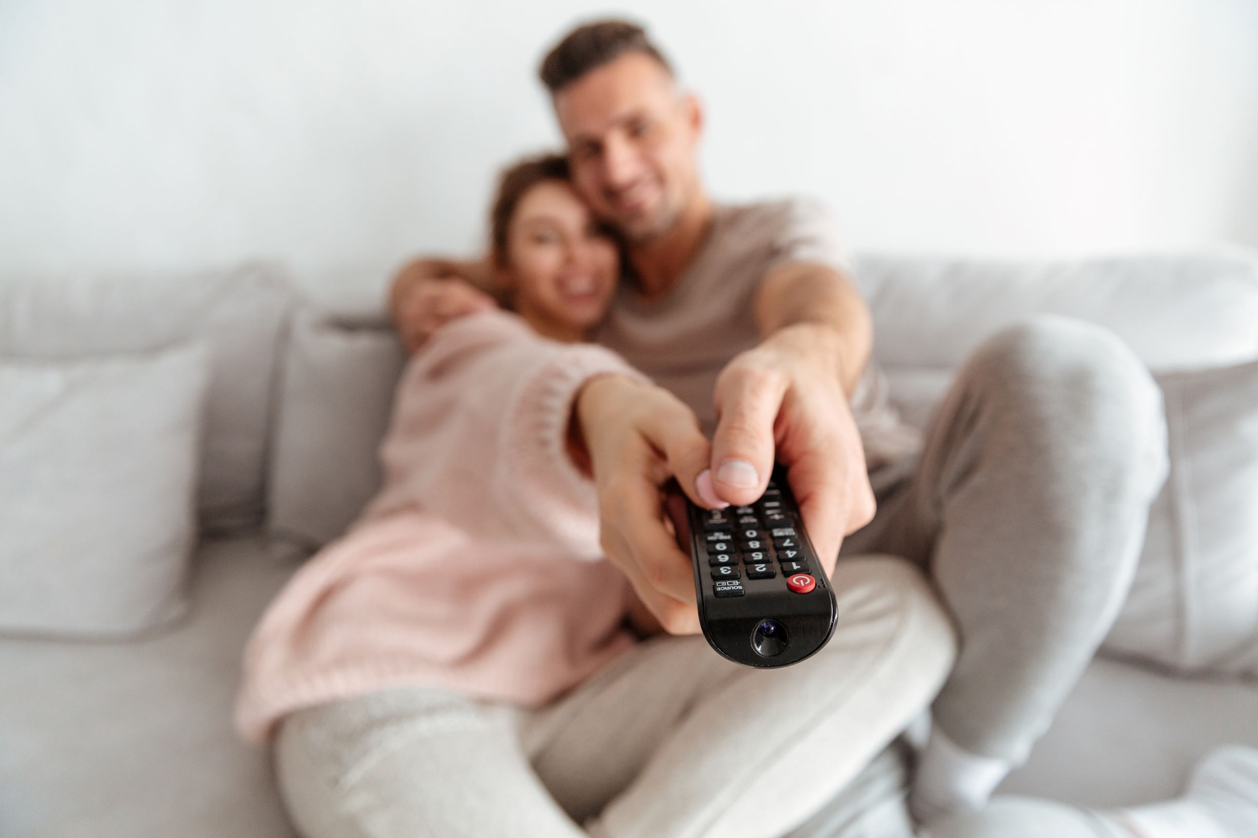 Couple with remote on the couch
