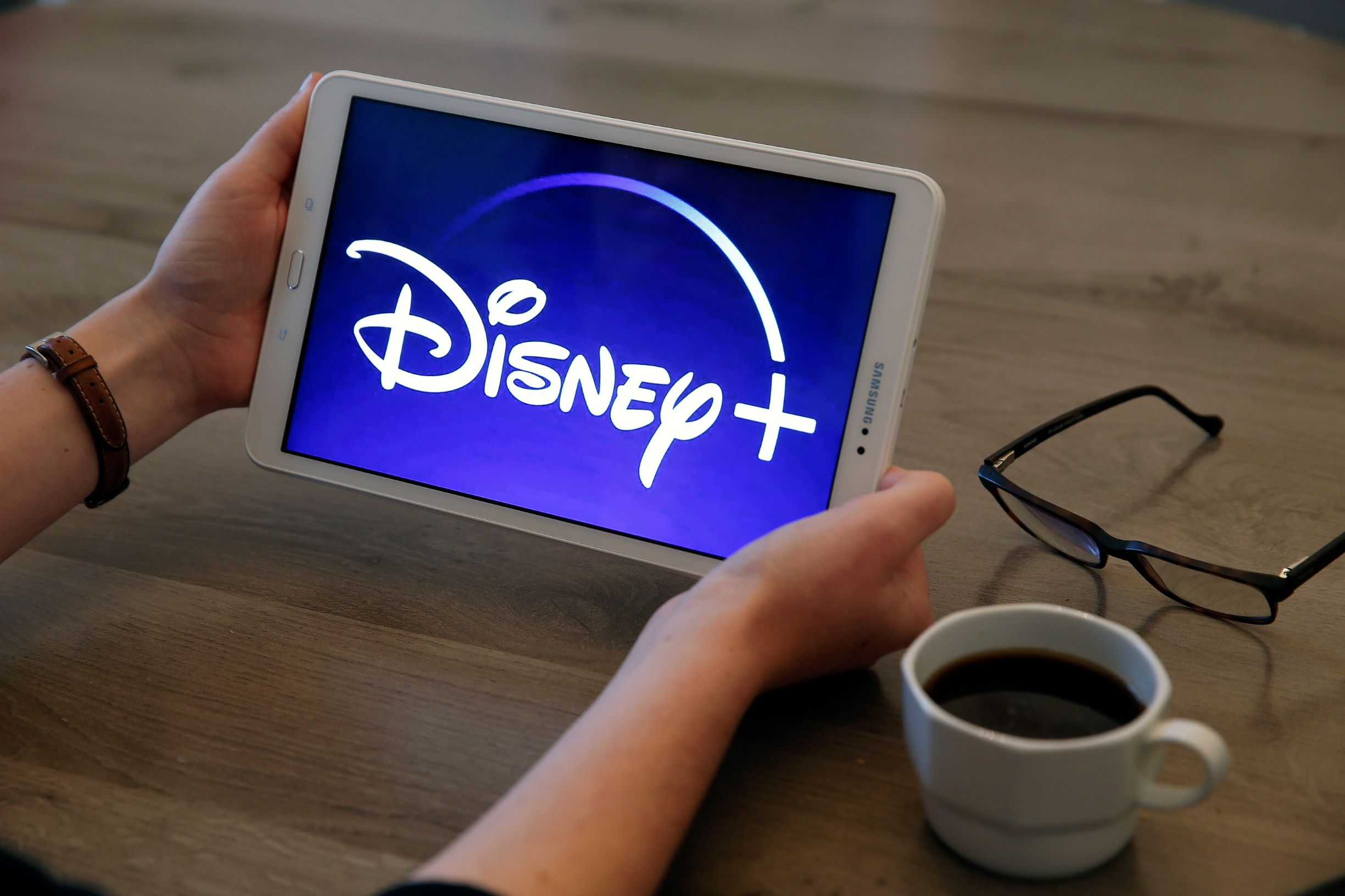 Streaming-Blog-Disney-Plus-Logo-on-Tablet-Being-Held-Next-to-coffee-on-table.jpg