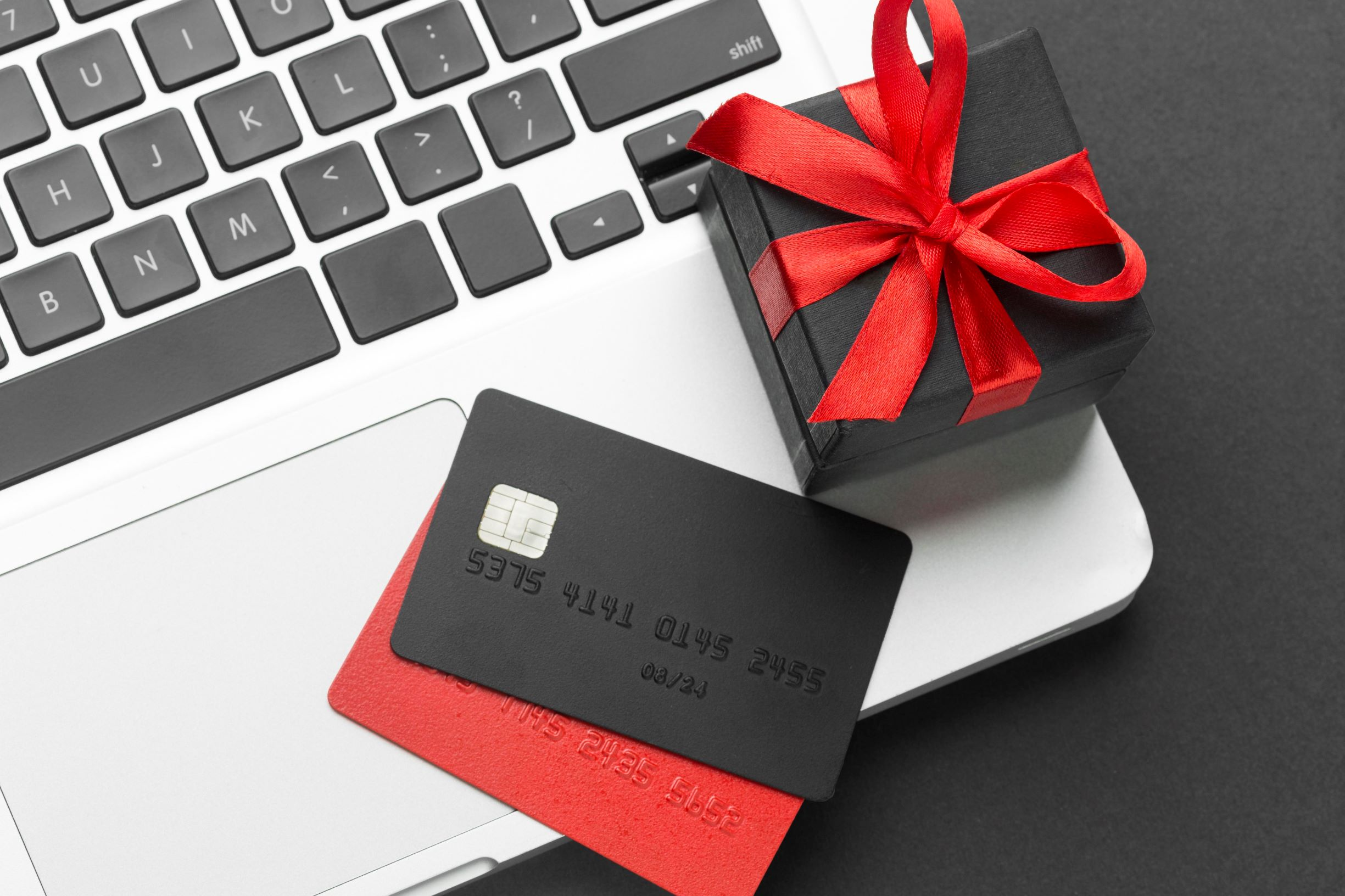 Credit cards sitting on edge of laptop