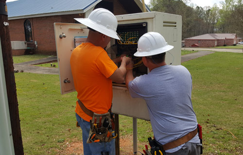 Technicians make a connection in a fiber distribution cabinet.