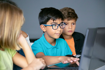 Boy typing on laptop with classmates sitting at table
