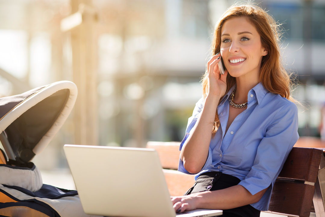 Photo of business woman in public talking and using laptop
