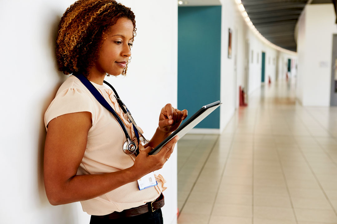 Photo of young female physician using tablet in office hall