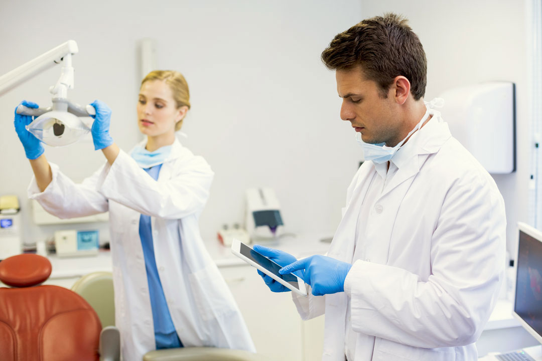 Photo of male dentist adjusting room lights with tablet