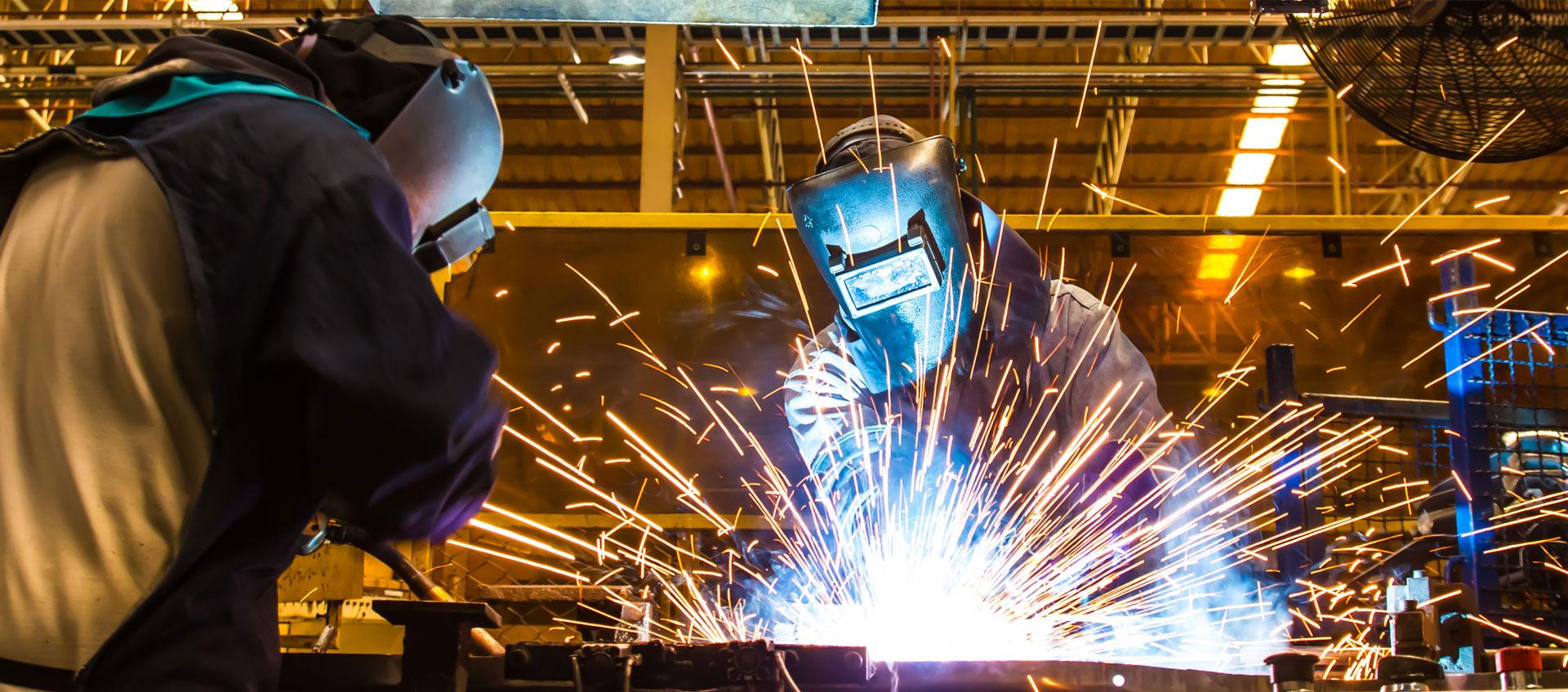 Photo of factory workers welding