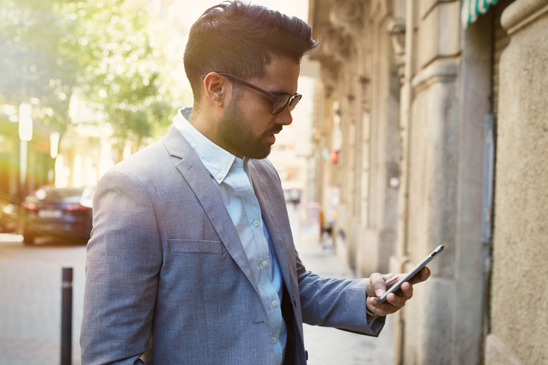 Photo of businessman looking at notification on mobile phone