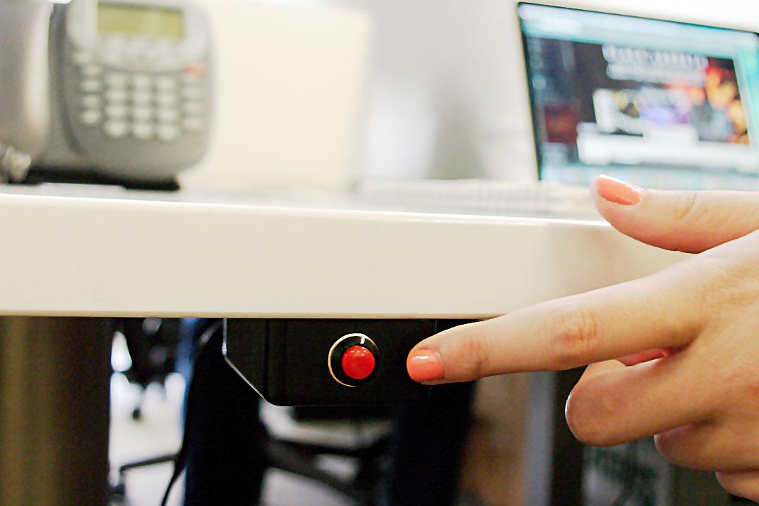 Photo of female employee pushing panic button under desk