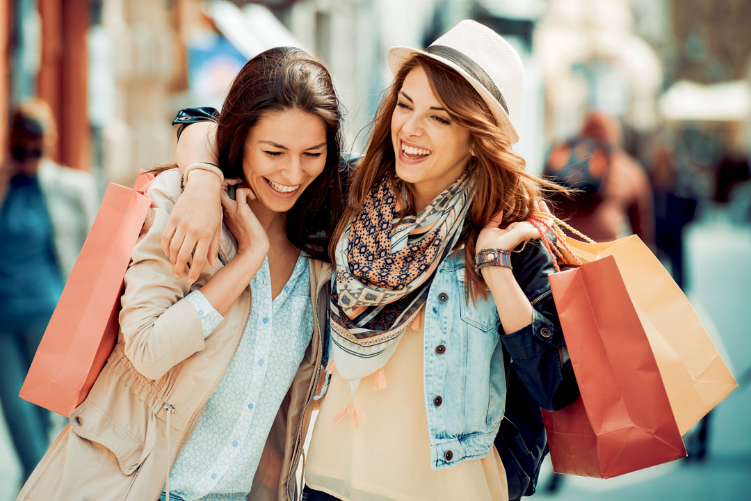 Photo of female shoppers leaving retail store with purchases