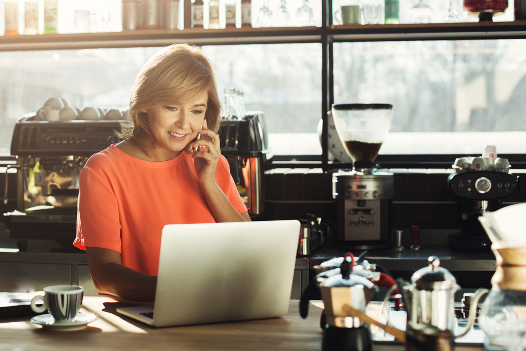 Photo of female business owner using laptop while on phone