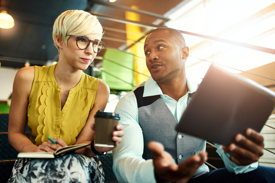 Photo of young business man and woman discuss app on tablet
