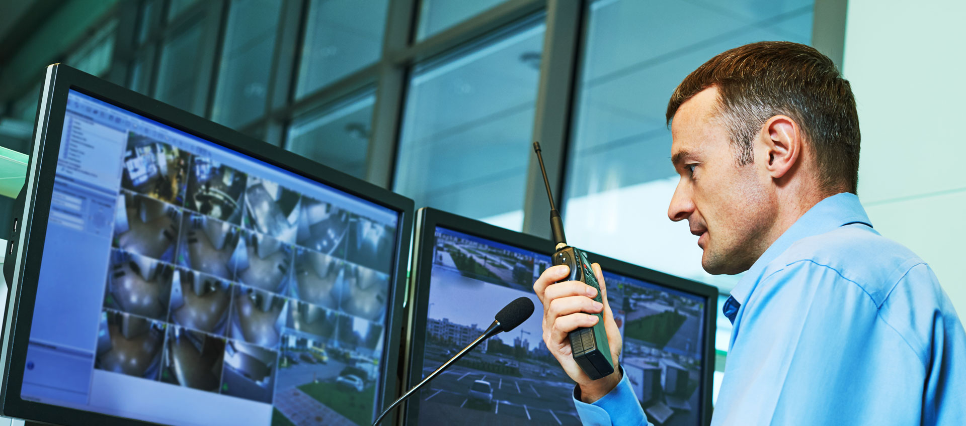 Photo of middle-age security officer using two-way radio