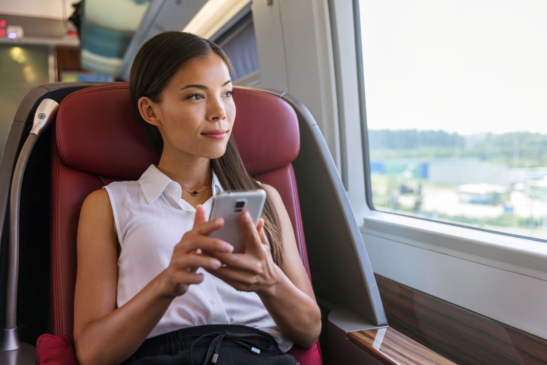 Photo of business woman away on train using mobile phone