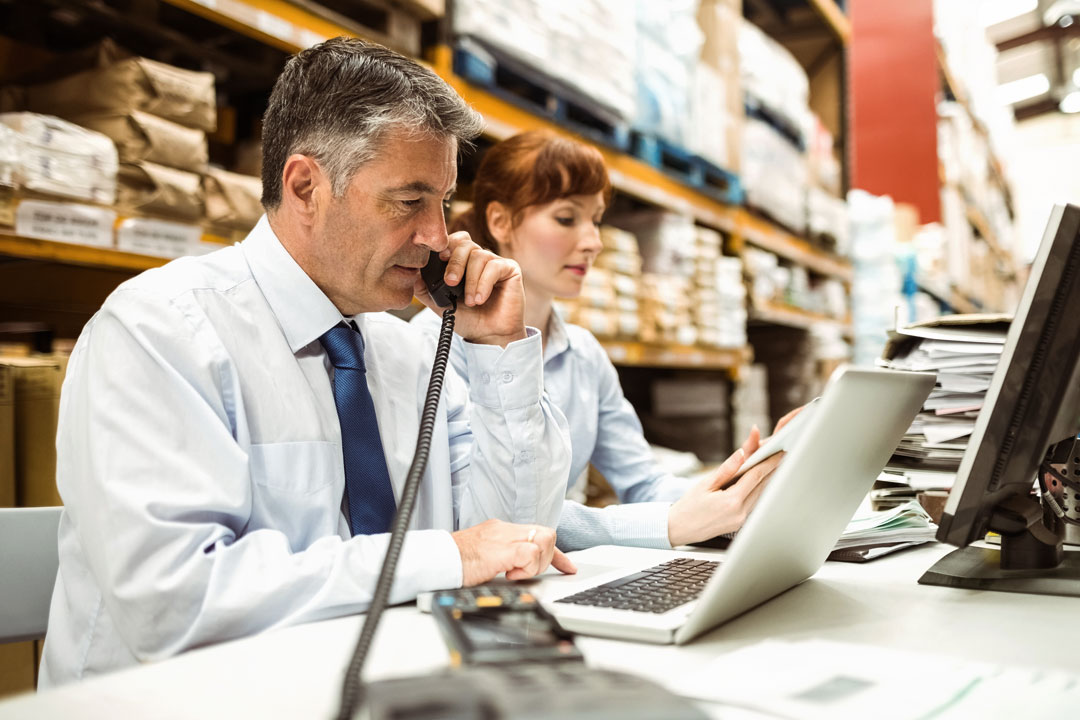 Photo of warehouse manager on phone while using laptop