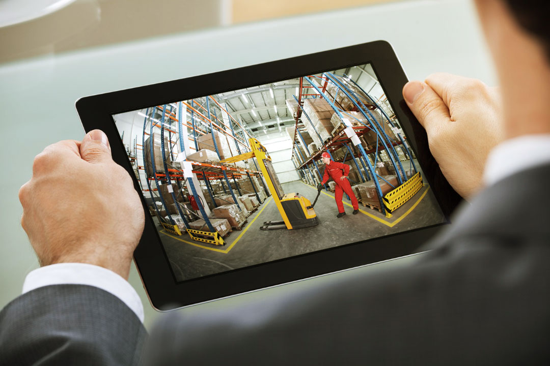 Photo of businessman watching live feed of inventory warehou