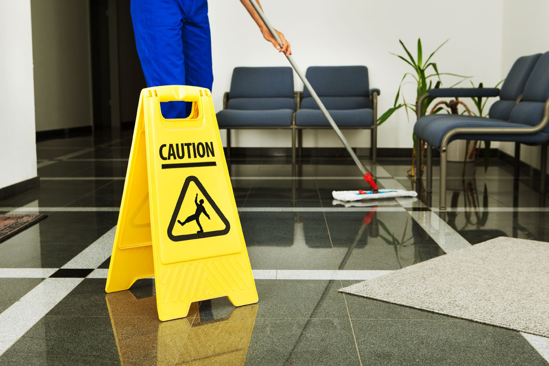 Photo of custodian mopping, with wet floor sign in foregroun