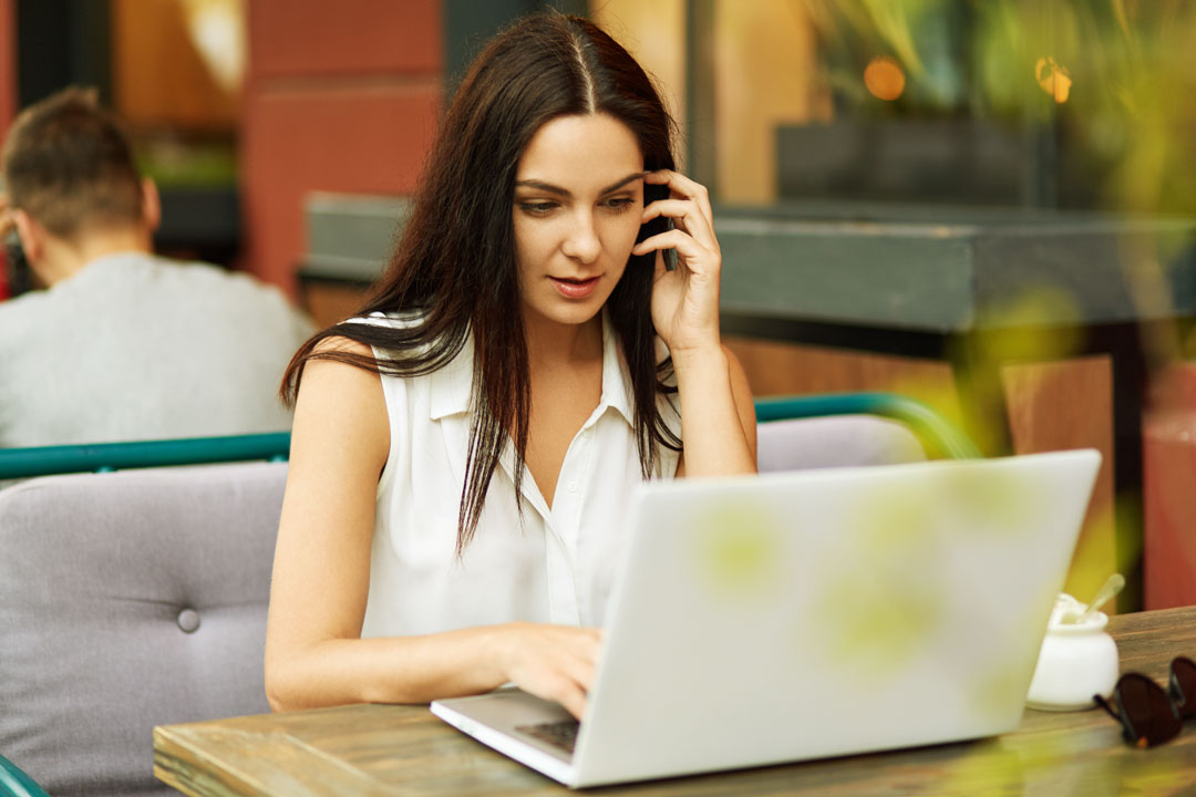 Photo of business woman using laptop outside at cafe