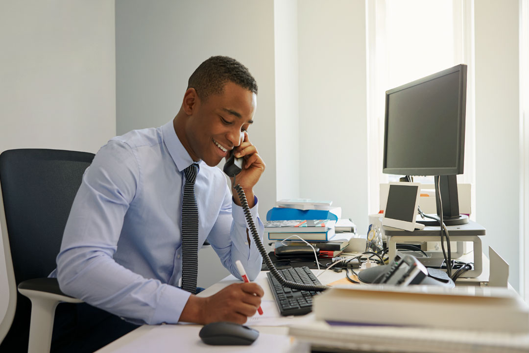 Photo of happy businessman talking on phone in office