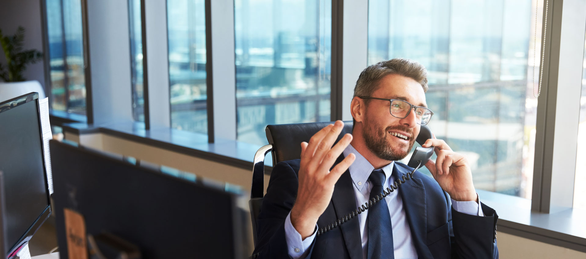 Photo of businessman talking on phone in high-rise office