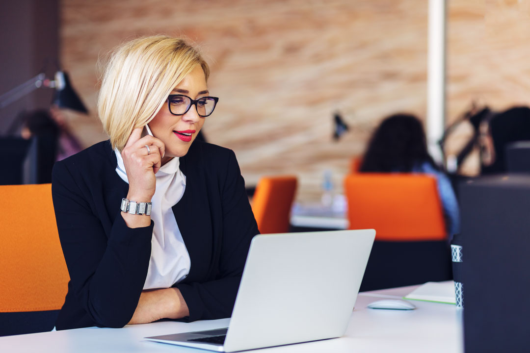 Photo of young business woman using phone and laptop