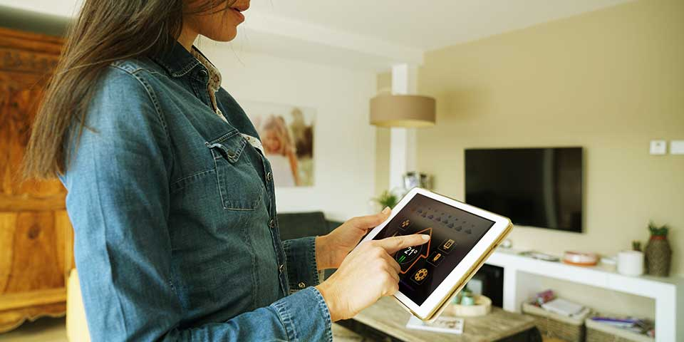 Photo of woman controlling thermostat on tablet