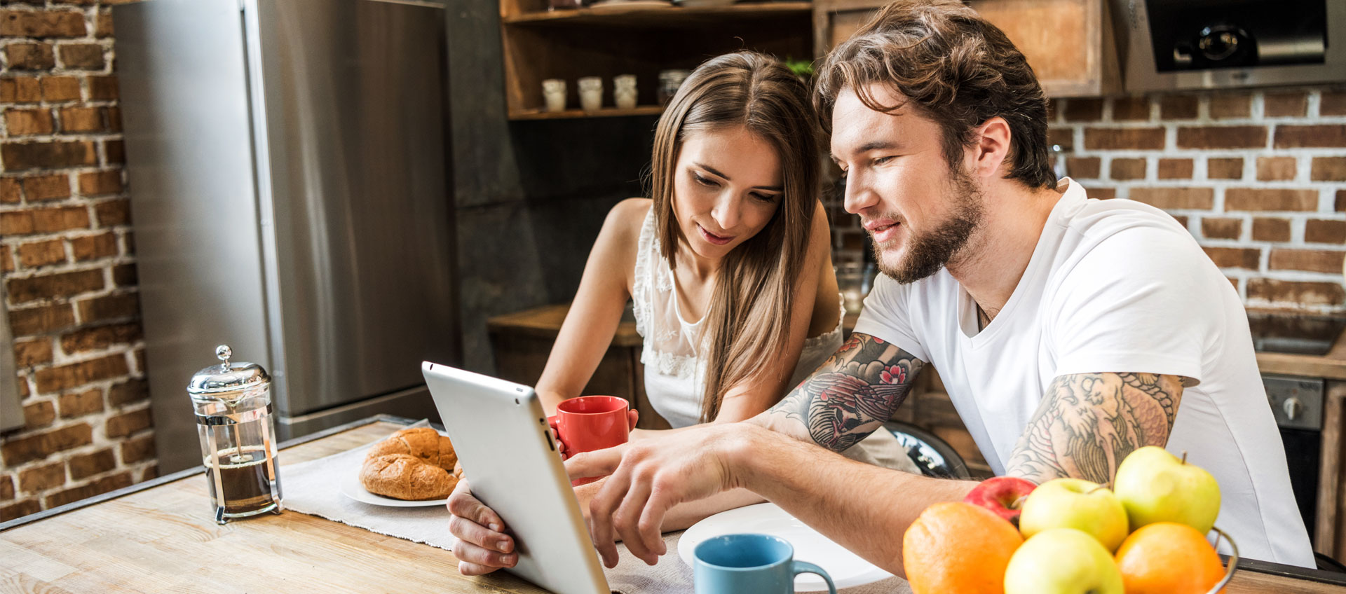 Photo of young couple looking at tablet and eating breakfast