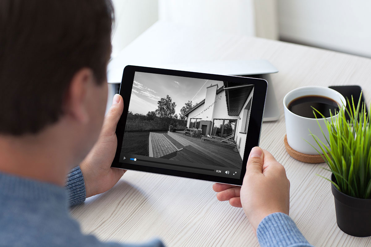 Photo of a man using a tablet to view surveillance video
