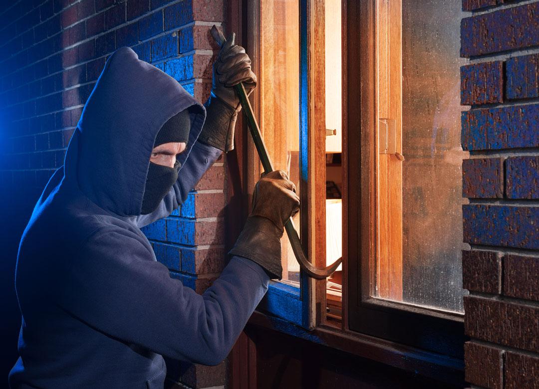 Photo of burglar breaking in through window