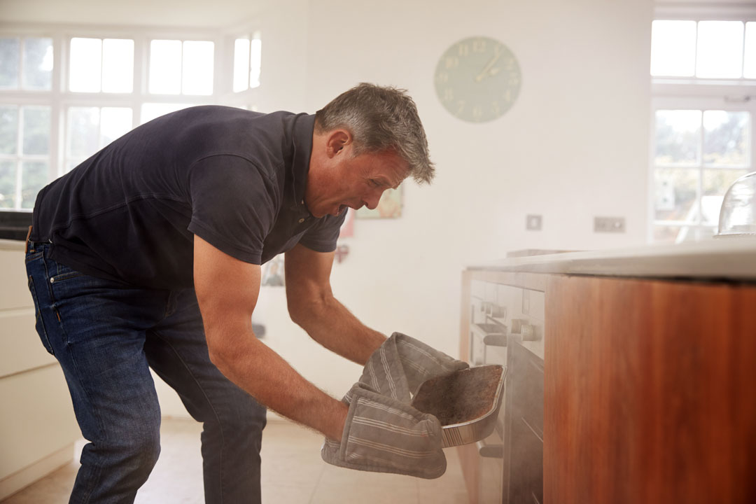 Photo of a man frantically pulling burning food from oven