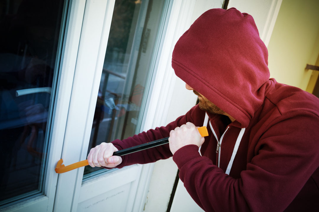 Photo of a man using a crowbar to break into a home