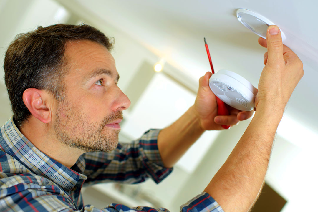 Photo of a man replacing a smoke detector battery