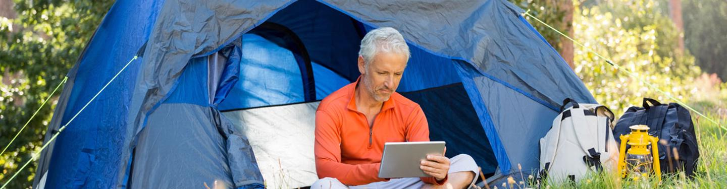 Photo of a man using tablet at a camp site
