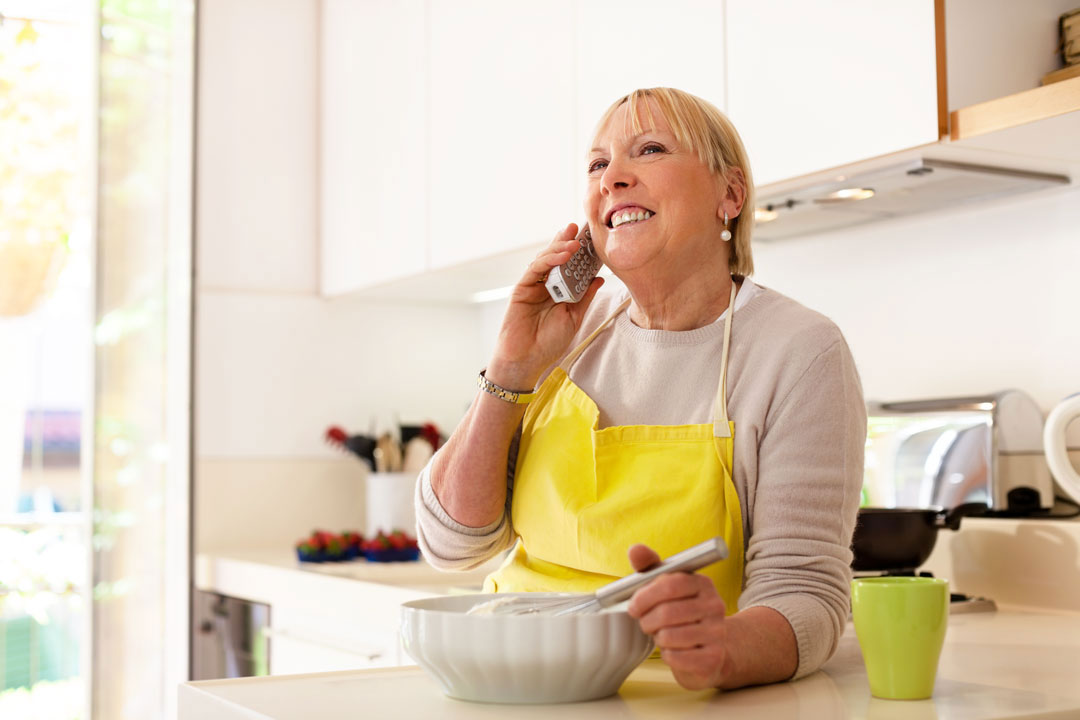 Photo of woman talking on phone while cooking