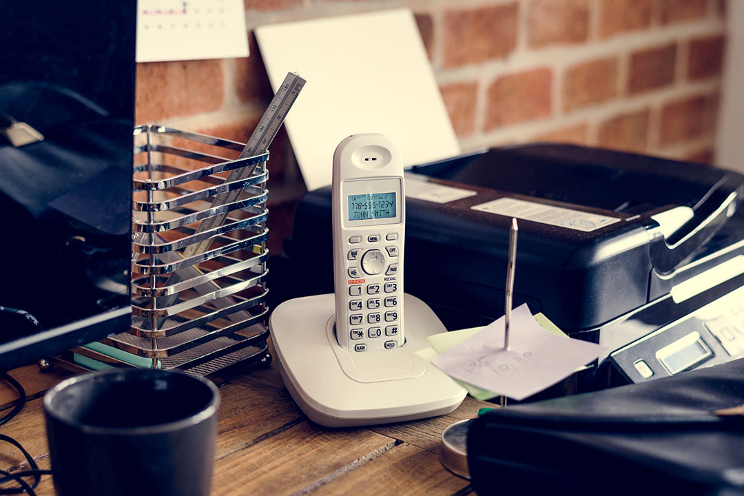 Photo of desk phone with caller information displayed