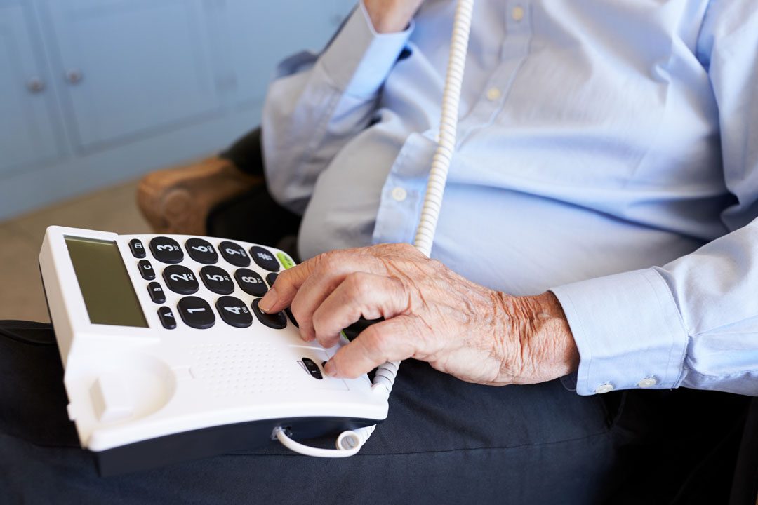 Photo of senior man using phone with large buttons