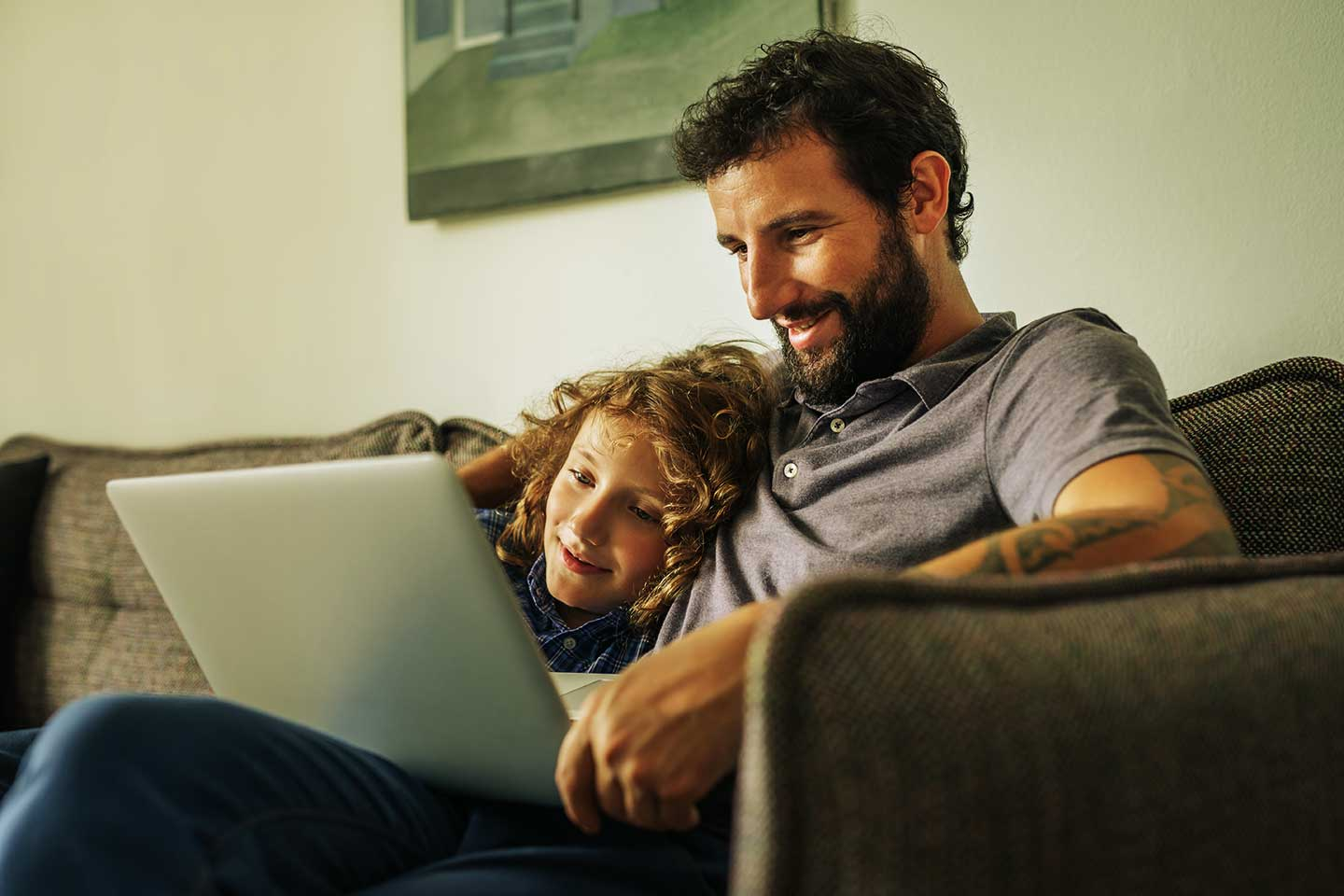 Photo of father and son streaming video on laptop