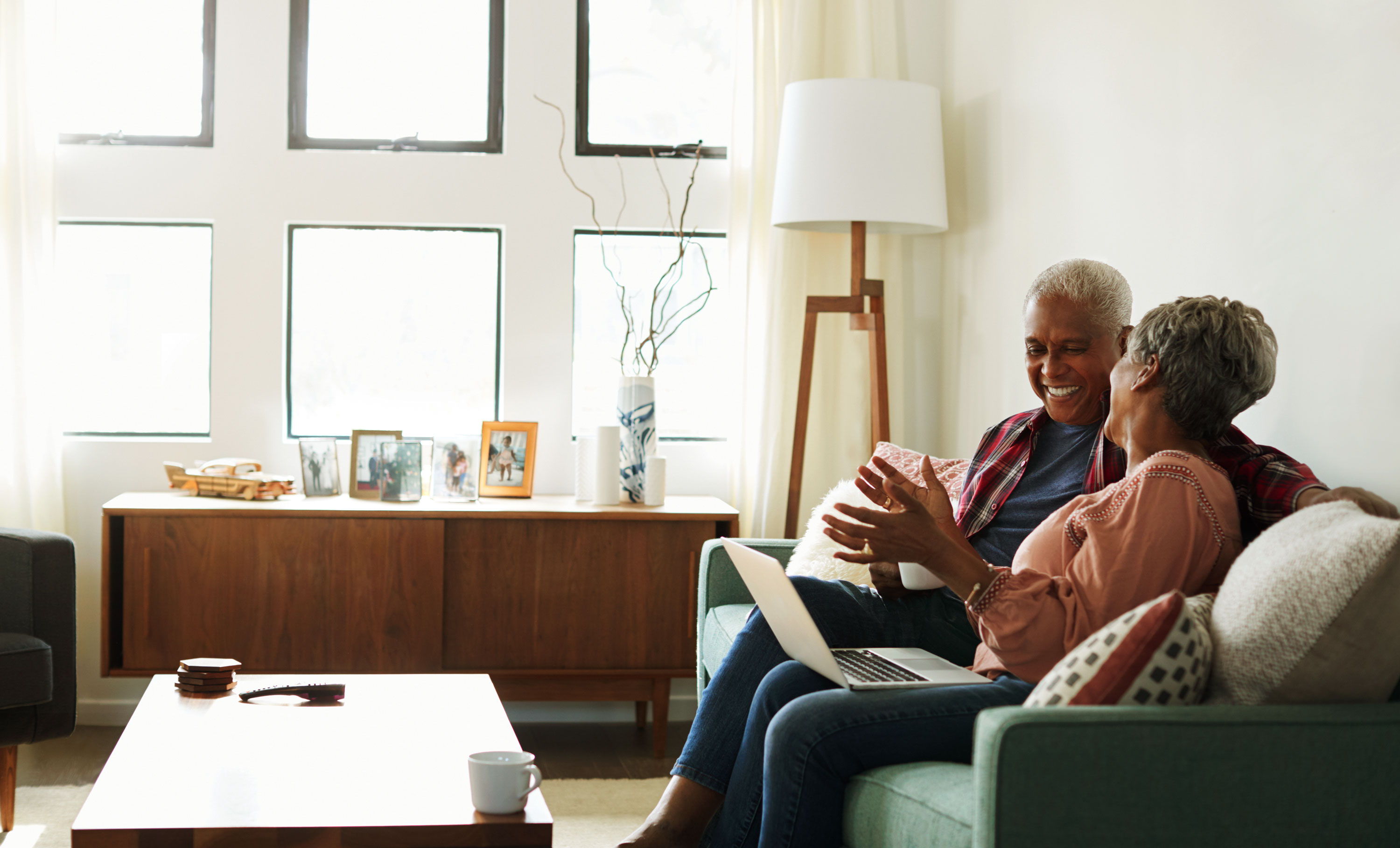 Photo of senior couple using laptop on couch